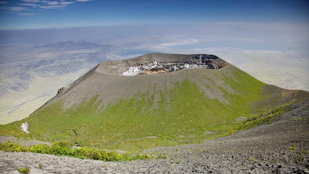 Ol Doinyo Lengaï, volcan actif du rift africain en Tanzanie. En arrière-plan: bordure de la vallée du grand rift et lac Natron. Un air de la Limagne d'il y a 19 millions d'années.